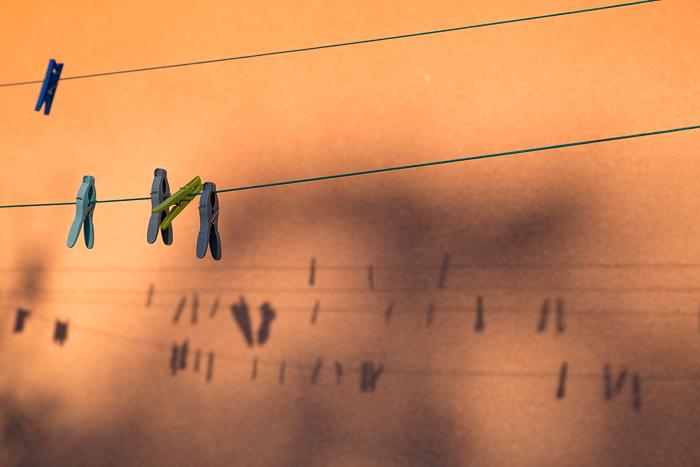 Pinces et cordes à linge et leurs ombres sur un mur orange