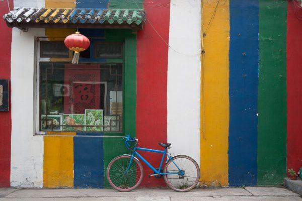 Bicyclette bleue posée contre un mur colorée en Chine