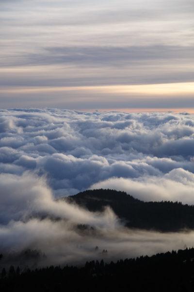 Des nuages enveloppent les sommets des montagnes alpines au coucher du soleil