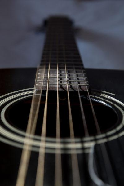 Corde d'une guitare folk noire en train de vibrer