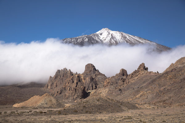 Le volcan El Teide enneigé avec les rochers Roques de Garcia devant