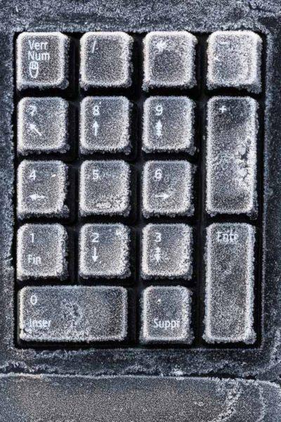 Obsolescence programmée : clavier d'ordinateur jeté, recouvert de givre.
