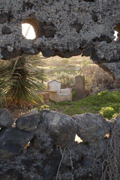 Fauteuil usé et abandonné vu à travers un trou dans un vieux mur