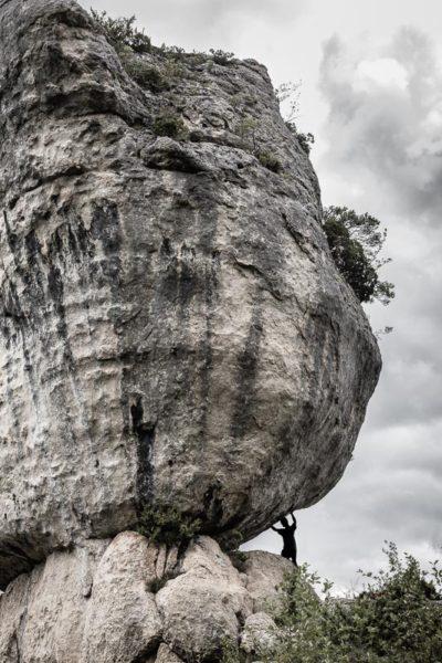 Une silhouette semble tenir à bout de bras un énorme rocher. Une image faisant penser au mythe de Sisyphe.