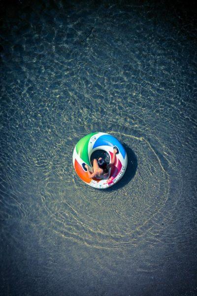 Baignade, jeune femme dans une grande bouée, se baignant dans une rivière. Photographie vue de haut.
