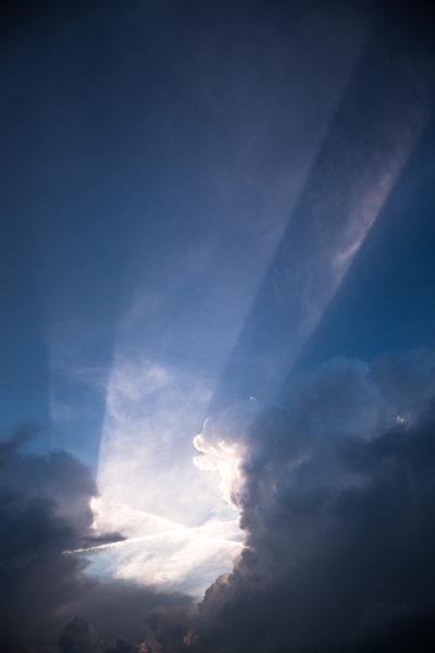 Des rayons de soleil passe à travers les nuages dans un ciel menaçant.