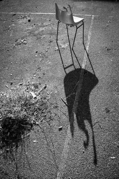 Une chaise cassée et abîmée projette une ombre sur le macadam. Une ombre qui fait penser à un motif du peintre Jean Arp. Ambiance urbex.