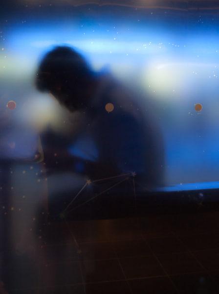 Silhouette d'un homme à travers une vitre, dans une ambiance bleue