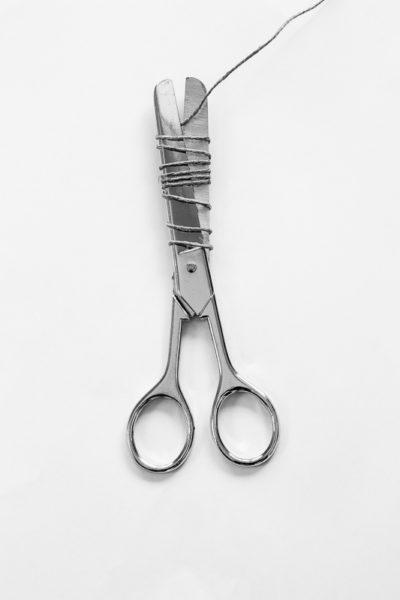 Une ficelle enroulée autour d'une paire de ciseaux
