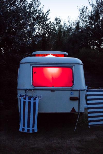 La nuit tombe sur le camping, une caravane est éclairée.