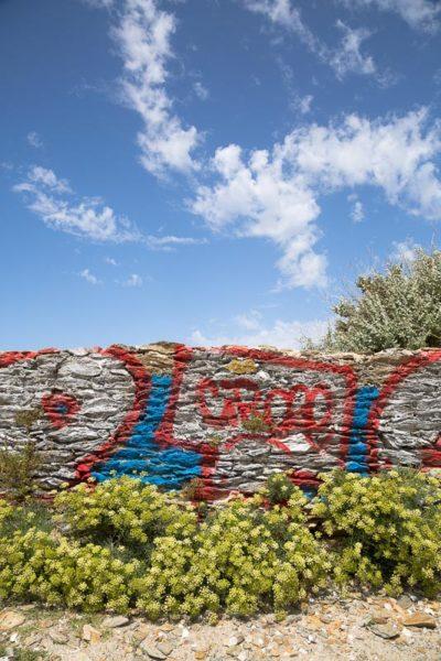 Graffiti sur un vieux mur sous un ciel bleu et quelques nuages blancs