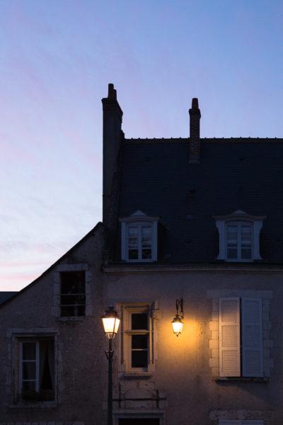 Lampadaires allumés devant une façade d'immeuble alors que la nuit tombe