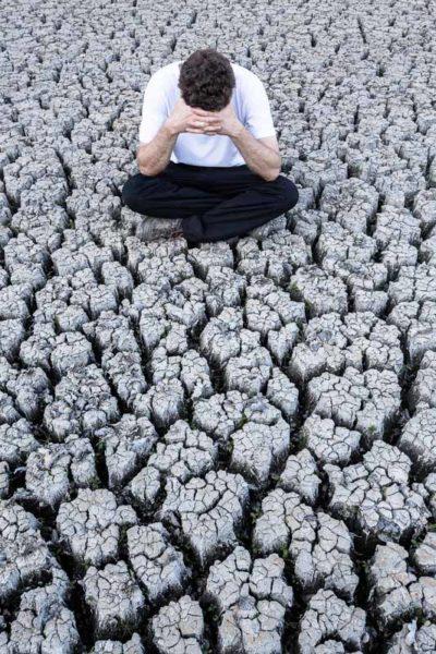Un homme assis sur une terre sèche et craquelée, se tient la tête