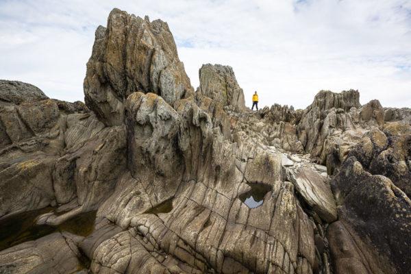 Silhouette d'un homme dans un chaos de rochers, en bord de mer