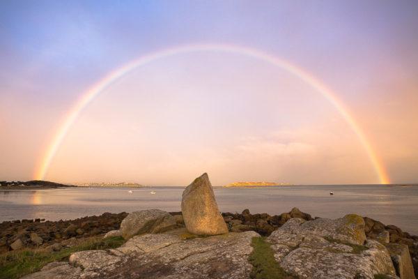 Arc-en-ciel au-dessus de la mer et d'un faux menhir en Bretagne